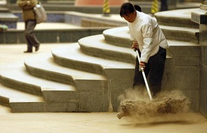 A cleaner clears away sand from an overnight sandstorm originating on the border of China and Mongolia which covered Beijing, 17 April 2006. Millions of Beijing residents woke up to find their city covered in sand -- another reminder that the desert is moving closer to the Chinese capital. (Peter Parks/AFP/Getty Images)