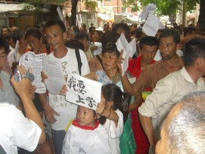 """A young petitioner holds a sign reading, """"I want to go to school."""" (The Epoch Times)"""