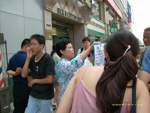 A tragedy of selling a daughter was put on show in the busy street of Beijing. (Feng Changle/The Epoch Times)