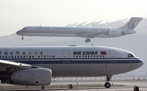 A China Eastern Airlines plane lands as an Air China jetliner waits to take off at the Beijing Capital International airport, 04 November 2006. (Goh Chai Hin/AFP/Getty Images)