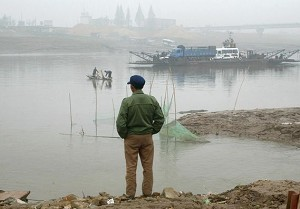 A farm worker, waiting for the ferry that would carry him across Dongting Lake, on October 31, 2004. (Frederic J Brown/AFP/Getty Images)