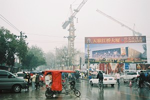 A corner in downtown Beijing. Old Hutongs get demolished, and turned into modern buildings as displayed on the billboard.  (Yodo Soma)