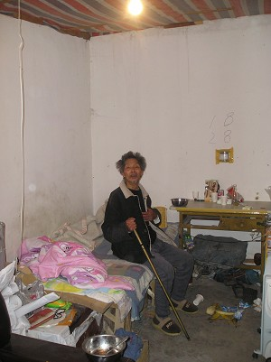 Rattling his stick in anger, Liu Fengchi tells of his experience, from his room with a vinyl sheet roof. (Yodo Soma)