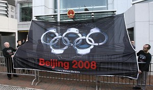 A large flag showing the Olympic rings transformed into handcuffs was unfurled outside the Liaison Office of China in  Hong Kong by five representatives of the rights group Reporters Without Borders (RSF) to mark Human Rights Day, Dec. 10. (MIKE CLARKE/Getty Images)