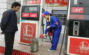 A man waits as his container is filled with petrol by an attendant at a Sinopec station outside of Yichang, November 26, 2007, in central China's Hubei province. China has filled its first national oil reserve, the Zhenhai National Oil Reserve Base. (Frederic J. Brown/AFP/Getty Images)