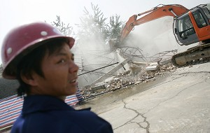 Workers demolish buildings with an excavator in Beijing, China.  (China Photos/Getty Images)