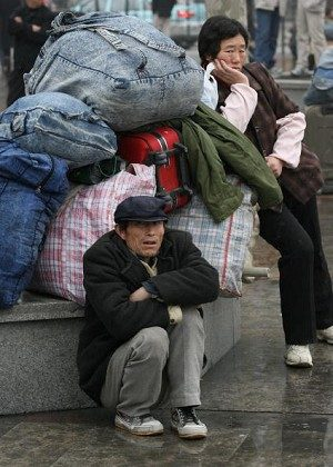 Chinese migrant workers and their families wait to board a train. (Mark Ralston/AFP/Getty Images)