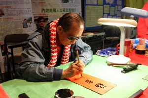Hong Kong rights leader Szeto Wah writes Chinese New Year couplets for Hong Kong residents at the Lunar New Year Market in Victoria Park. Szeto took part in an eight-month investigation into espionage by the Chinese communist regime. (Wu Lianyou/Epoch Times)
