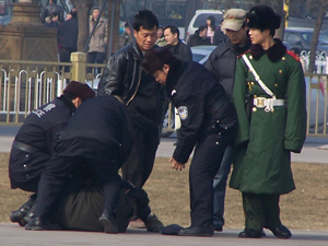 Police hold a man on the ground while kicking and beating him. (Minghui Net)