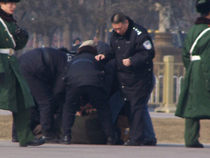 Police beat a man while shielding onlookers from seeing. (Minghui Net)