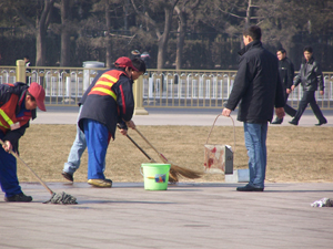 Workers wash away the blood stains. Their portable trash bins are covered with blood. (Minghui Net)