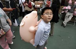 Hong Kong-A boy carries a pink pig-shaped balloon. (Mike Clarke/AFP Photo)