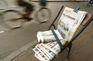 Cyclists pass newspapers on sale on a street in Beijing. The Propaganda Department of the Chinese Communist Party (CCP) announced plans to further tighten control of print media through grading system. (Peter Parks/AFP/Getty Images)