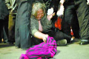 Elderly woman strips as people jeer. (Photo from Internet)