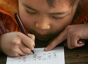 A boy is writing Chinese characters. (Getty Images)