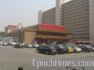The curio shopping mall on the north side is located 30 meters away from Gao's home.  Judging by the vehicle number plates at least one third of the cars parked there belong to the police monitoring Gao's family. (The Epoch Times)