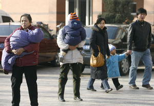 Women carry children dressed for the cold as a family walks past in Beijing. (Frederic J. Brown/AFP/Getty Images)