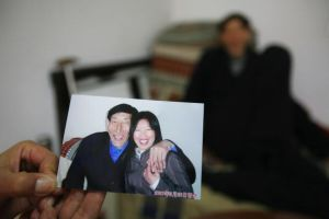 Bao Xishun shows pictures of his happy new life with wife, Xia Shujuan. (China Photos/Getty Images)
