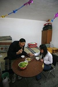 Bao Xishun,shares a meal with his bride. (China Photos/Getty Images)