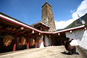 A Tibetan woman spinning on the roof of a traditional Tibetan house (Getty Images)
