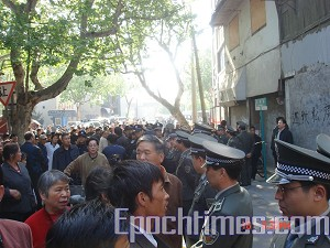 A crowd gathers to watch the forced eviction. (The Epoch Times)