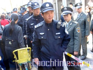 Police forcibly evict Yuan Aixiang from her home. (The Epoch Times)