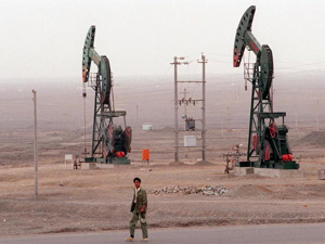 An oil worker walks past the Tuha petroleum fields in northwestern China's Xinjiang region. (Robyn Beck/AFP/Getty Images)