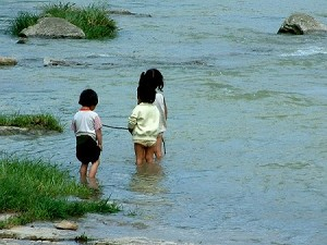 Children playing in the river during the day. Their families cannot afford to send them to school. (Ben Ben)