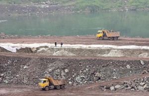 Two trucks dump earth on the construction of the Caojie hydropower station on Jialing River, a tributary of the Yangtze river, where water levels remain near historic lows, in Chongqing, China. (Liu Jin/AFP/Getty Images)