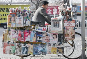 A Chinese cyclist rides past a bike-made newspaper stand on December in Beijing, China. (Guang Niu/Getty Images)