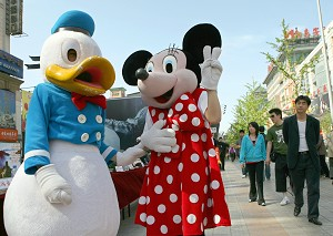 """Two Chinese travel agency workers wearing Walt Disney character Donald Duck and Minnie Mouse costumes in central Beijing, 20 April 2007. With its slogan """"Disneyland is too far,"""" Beijing's Shijingshan Amusement Park features a replica of Cinderella's Castle, staff dressed like Snow White and the Seven Dwarfs and other Disney images. (Teh Eng Koon/AFP/Getty Images)"""