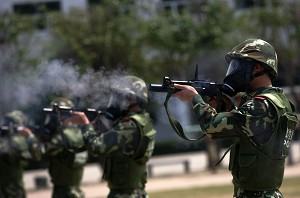 Soldiers firing their rifles in unison. (Getty Images)