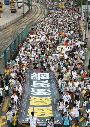 "Tens of thousands take part in a pro-democracy march in Hong Kong, July 1, 2006. The big banner carried by the marches in this photo says, ""Internet users want universal sufferage."" (Epoch Times)"