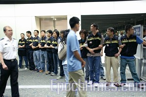 Customs officials form a human wall to prevent Falun Gong practitioners from entering Hong Kong. (The Epoch Times)