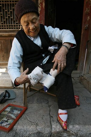 An elderly woman binds her feet in a long strip of silk cloth. (Getty Images)