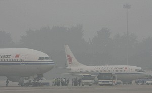 Passengers board an Air China plane as haze blankets the international Airport in Beijing. The OECD warned that China's breakneck economic growth was wreaking severe damage on the environment and efforts to date to curb pollution had been insufficient. (Teh Eng Koon/AFP/Getty Images)
