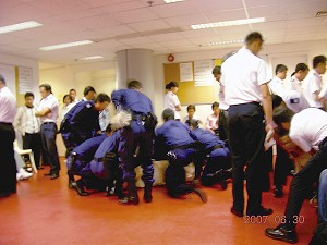 A Falun Gong adherent is being wrapped up in a police blanket by several policemen at the Hong Kong International Airport last weekend. In the right hand corner, a policeman is trying to pull a female adherent. (Epoch Times)