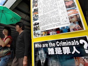 Two women in Hong Kong walk past placards denouncing the Chinese government's alleged mistreatment of Falun Gong followers, 30 June 2007, as Chinese dictator Hu Jintao visited the Special administrative Region for the 10th anniversary of its absorption by communist China. (Philippe Lopez/AFP/Getty Images)