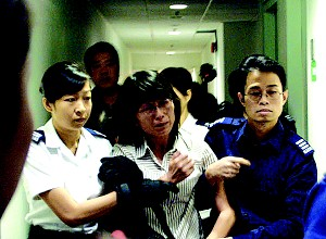 Police in Hong Kong force a Falun Gong adherent onto a departing flight soon after her arrival to attend pro-democracy events. (Epoch Times)