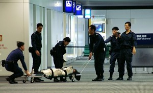 Wrapped up in a police blanket, a Falun Gong adherent is being taken to the plane. (Epoch Times)