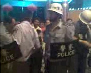 Protesters surround the local government offices as police respond. (The Epoch Times)