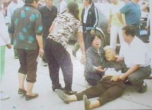 Zhang Shiying lies in the street after leaping to her death in an effort to save her son-in-law's home. (Liu Feiyue/The People's Observer)