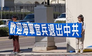 """Volunteers of the Global Service Center for Quitting the CCP hold a poster, """"We welcome officers and enlisted men to quit the CCP."""" (The Epoch Times)"""