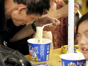 A family eats instant noodles at a fast food counter at a Beiijing railway station. (Peter Parks/AFP/Getty Images)