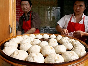 Chinese vendors prepare steaming pork buns at a sidewalk stall in Beijing. (Teh Eng Koon/AFP/Getty Images)