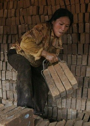 A woman stacks bricks in a factory in Henan, China. (Mark Ralston/AFP/Getty Images)