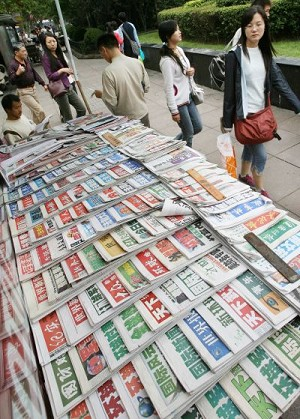 Chinese shoppers walk past a kiosk selling domestic Chinese newspapers at People's Square in Shanghai. According to the Hong Kong-based Information Center for Human Rights and Democracy, China has further tightened its control over media in the run-up to the Chinese Communist Party (CCP)'s 17th National Congress. (Mark Ralston/AFP/Getty Images)