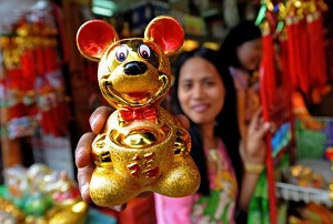 A vendor holds up a golden rat figurine at a street stall in Manila, Philippines. (Jay Directo/AFP/Getty Images)
