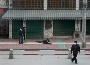 A man lies injured in the street March 14, 2008 during protests in Lhasa, Tibet. (phayul.com)