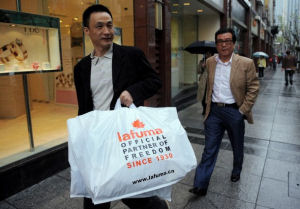 A Shanghai resident carries a bag full French brand Lafuma product.(Photo/Secret China)